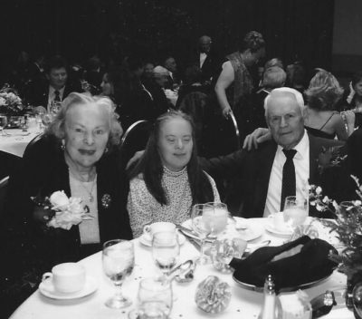The Campbell family happily sitting at a table during an event.