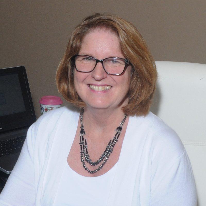 Nancy sitting at her desk smiling