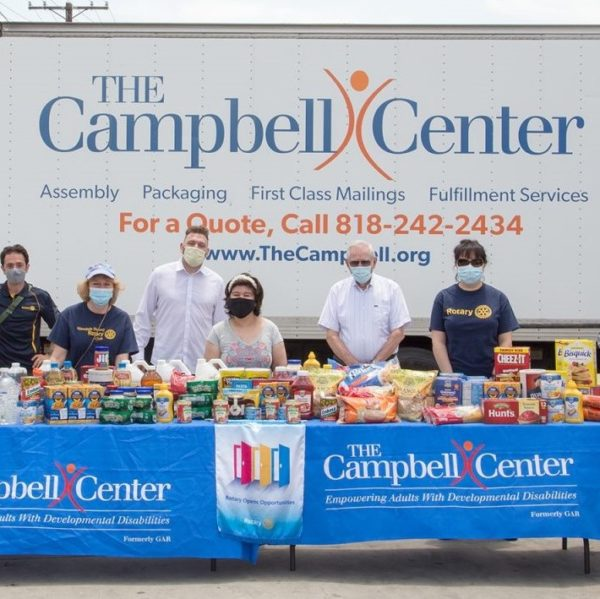 people standing in front of donated food