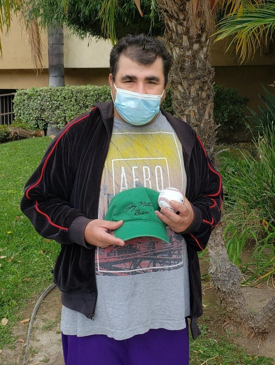 man with mask holding baseball hat and baseball
