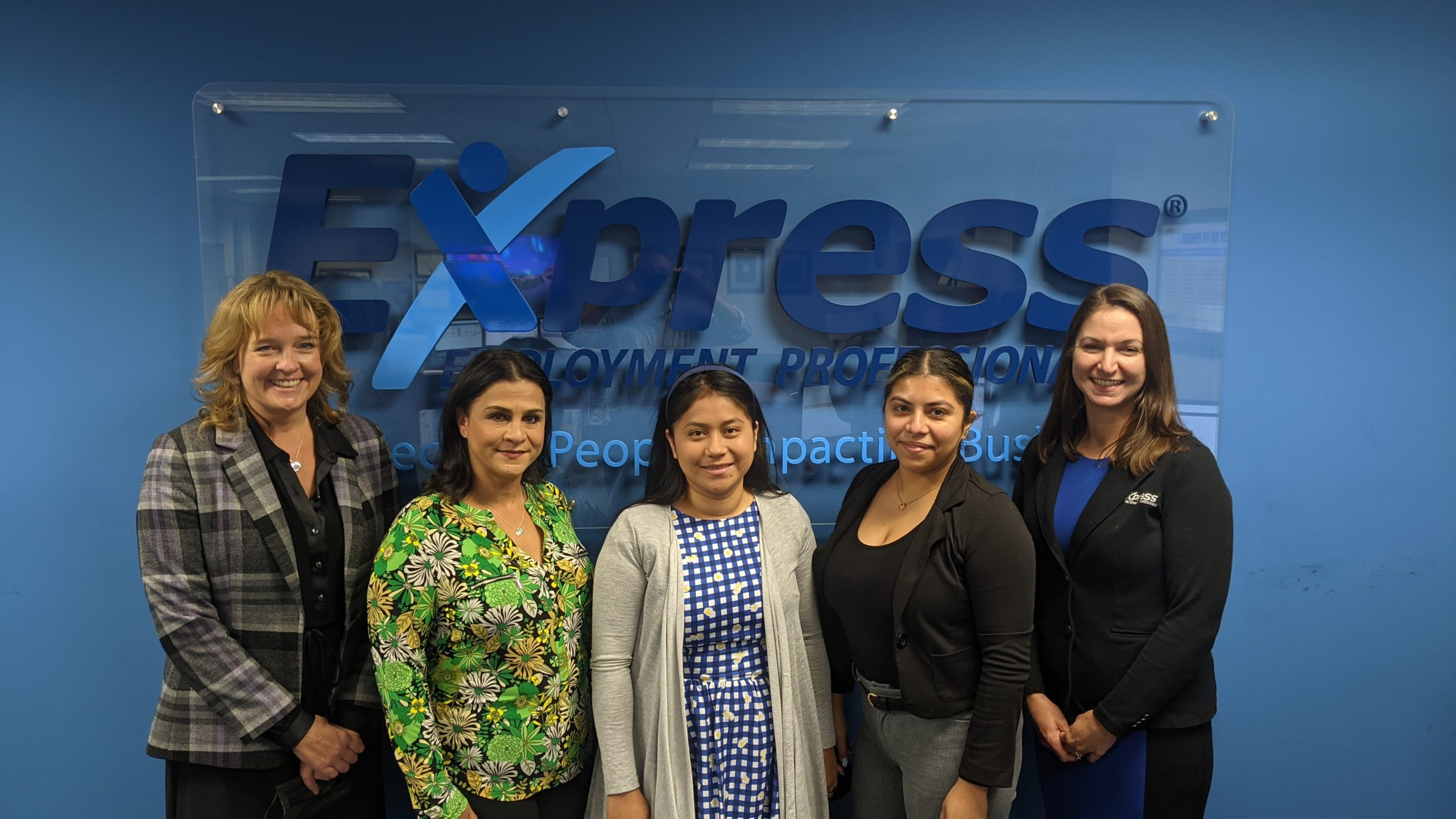 5 women standing in front of a business logo
