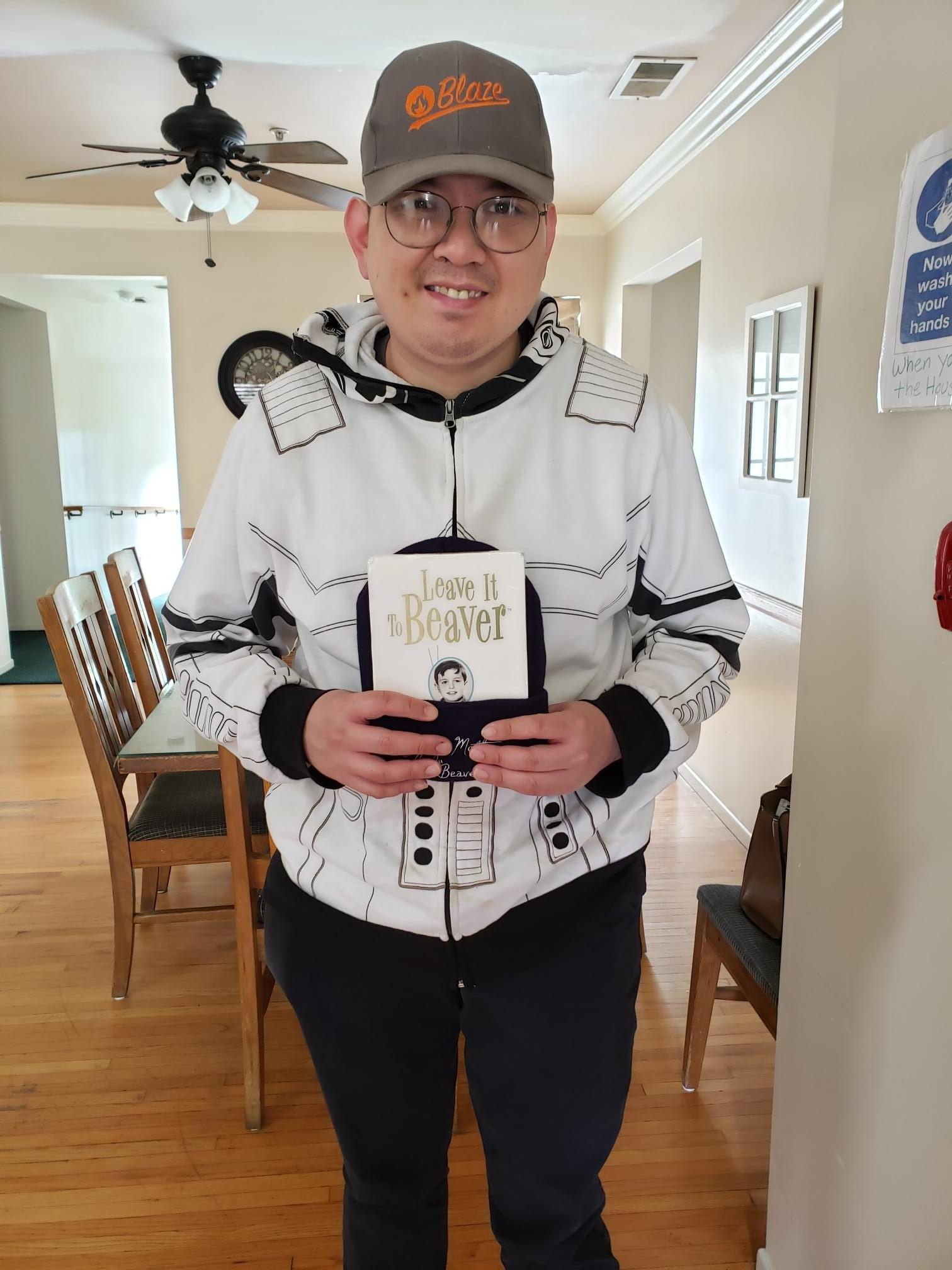 smiling man holding dvd & hat
